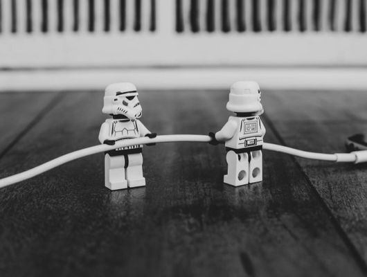 lego storm troopers pulling the charging cable out of an iphone... or maybe putting it in?