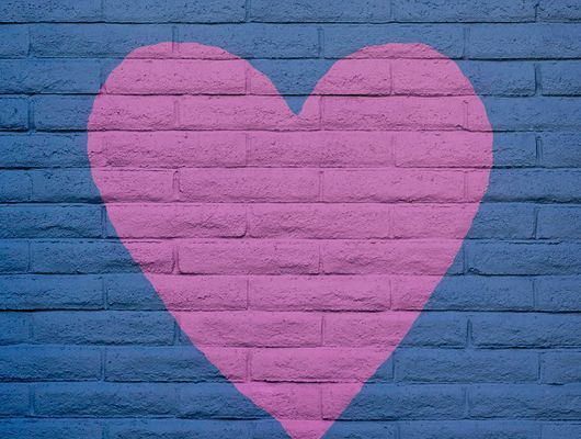 A pink heart painted over a purple brick wall outside representing the article